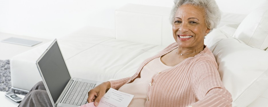Woman banking on her couch from a laptop