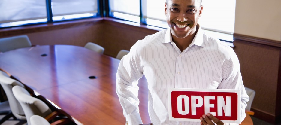 Happy small business owner holding open sign